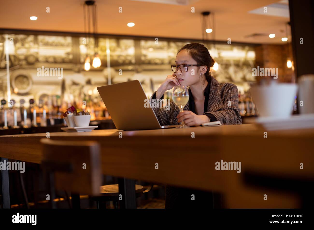 Female executive using laptop while having wine - Stock Image