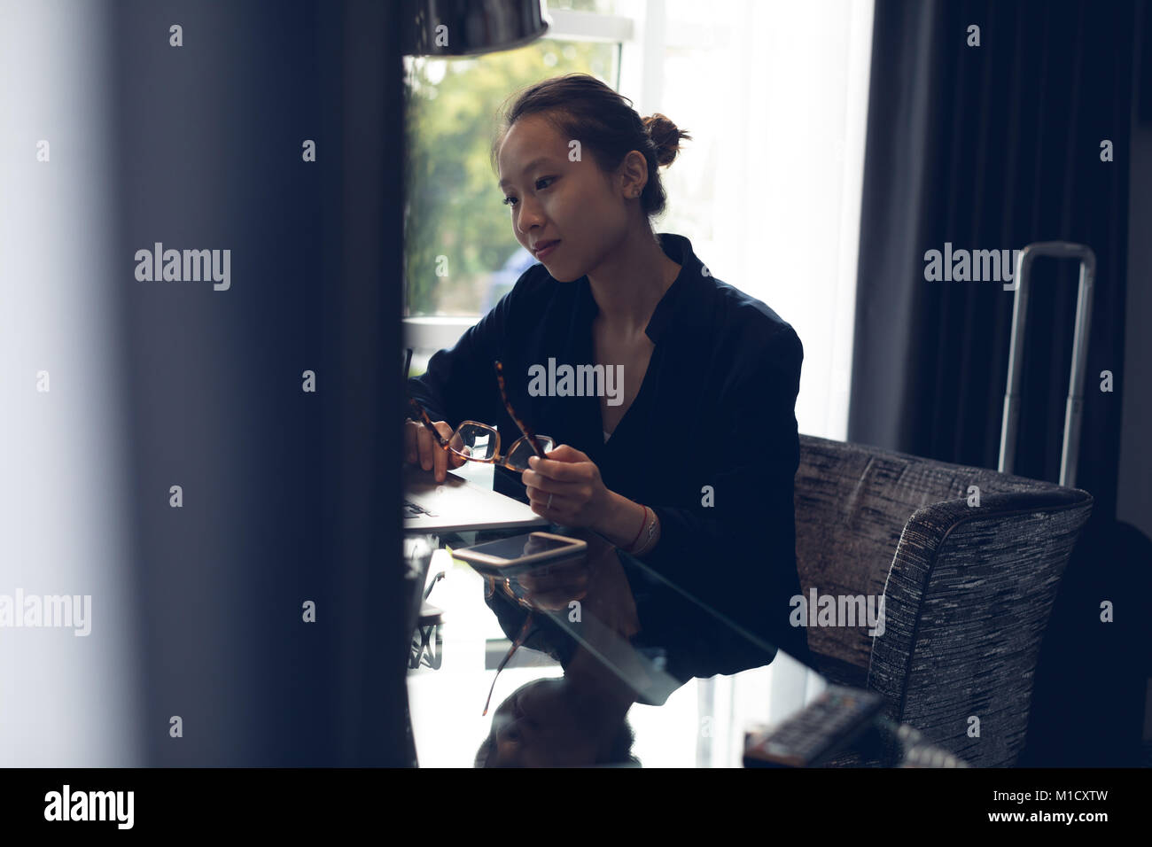 Thoughtful woman sitting with spectacles at table - Stock Image