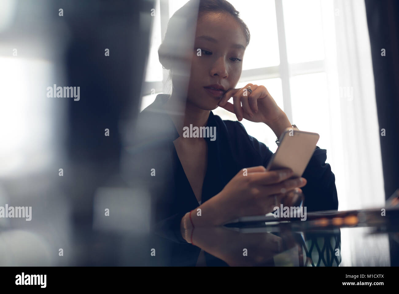 Woman using mobile phone at table - Stock Image
