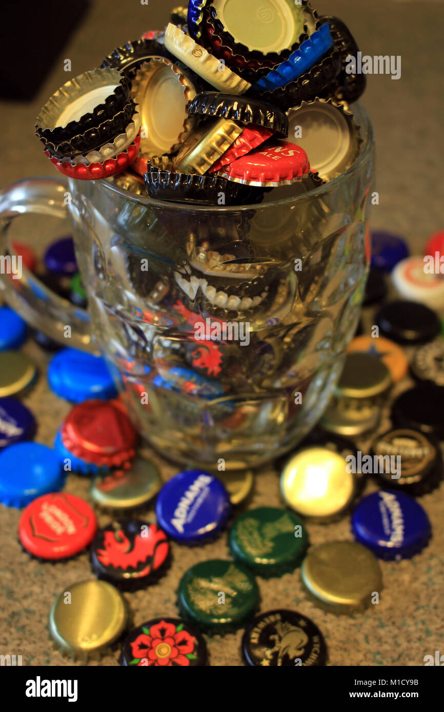 Used beer bottle tops collected after the beer has been drunk and are over flowing from a dimpled pint beer jug Stock Photo
