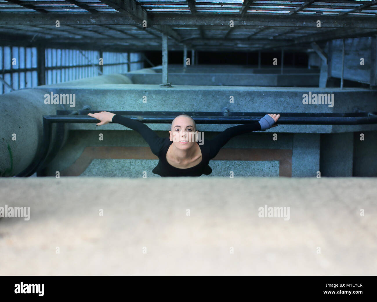 Beautiful bald woman looking up from the floor below and leaning on a railing - Stock Image