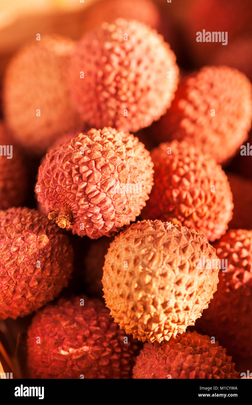 Full frame view of lychee fruits in a basket in late sunlight. - Stock Image
