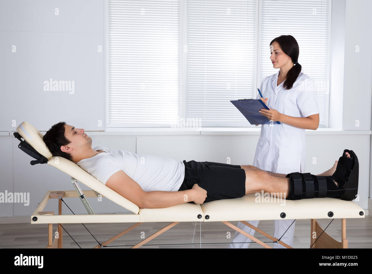 Young Female Orthopedist Standing Near Male Patient With Clipboard - Stock Image