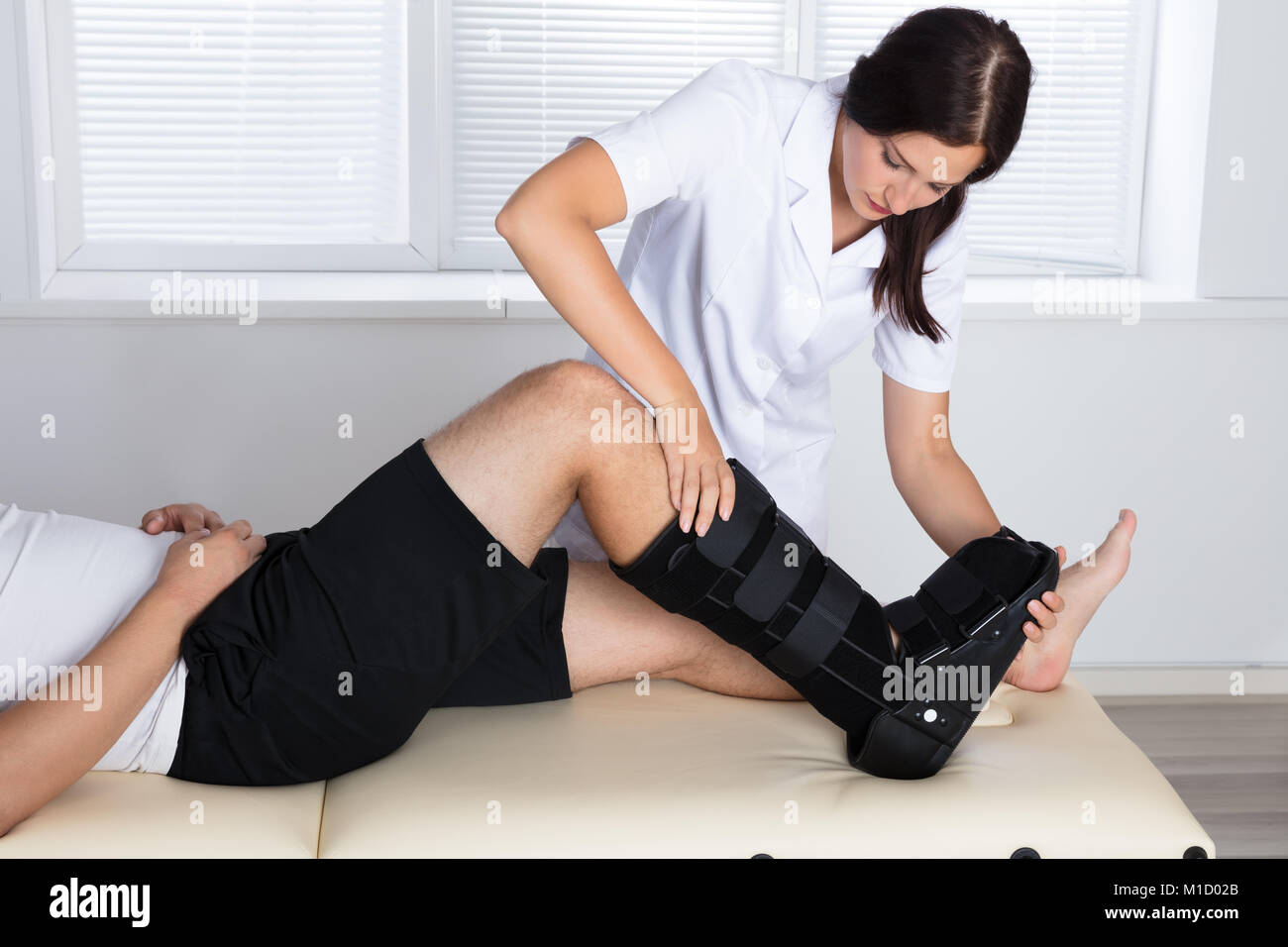 Young Female Orthopedist Adjusting Walking Brace On Patient's Leg In Clinic - Stock Image