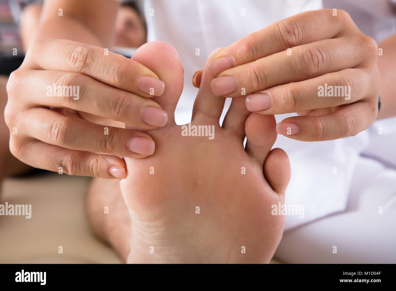 Close-up Of A Therapist's Hand Treating Person's Foot In Clinic - Stock Image