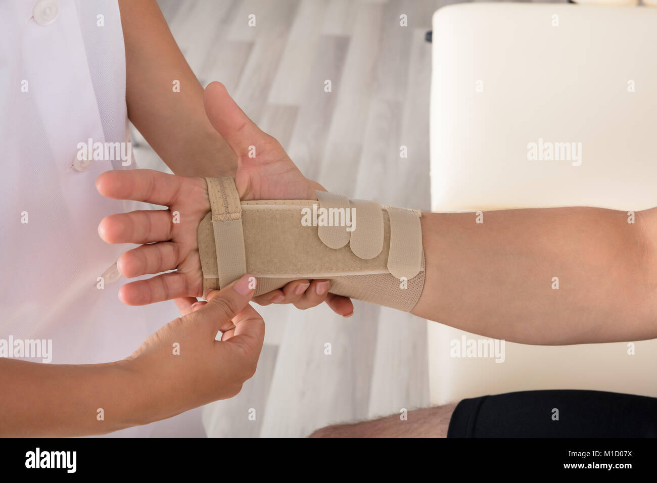 High Angle View Of A Orthopedist Fixing Plaster On Injured Person's Hand In Hospital - Stock Image