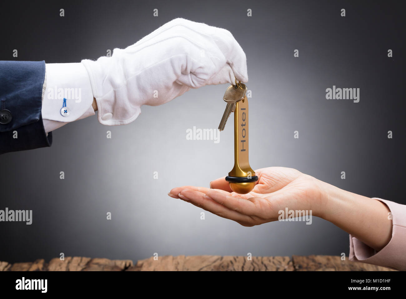 Close-up Of A Receptionist's Hand Giving Hotel Door Key To Customer - Stock Image