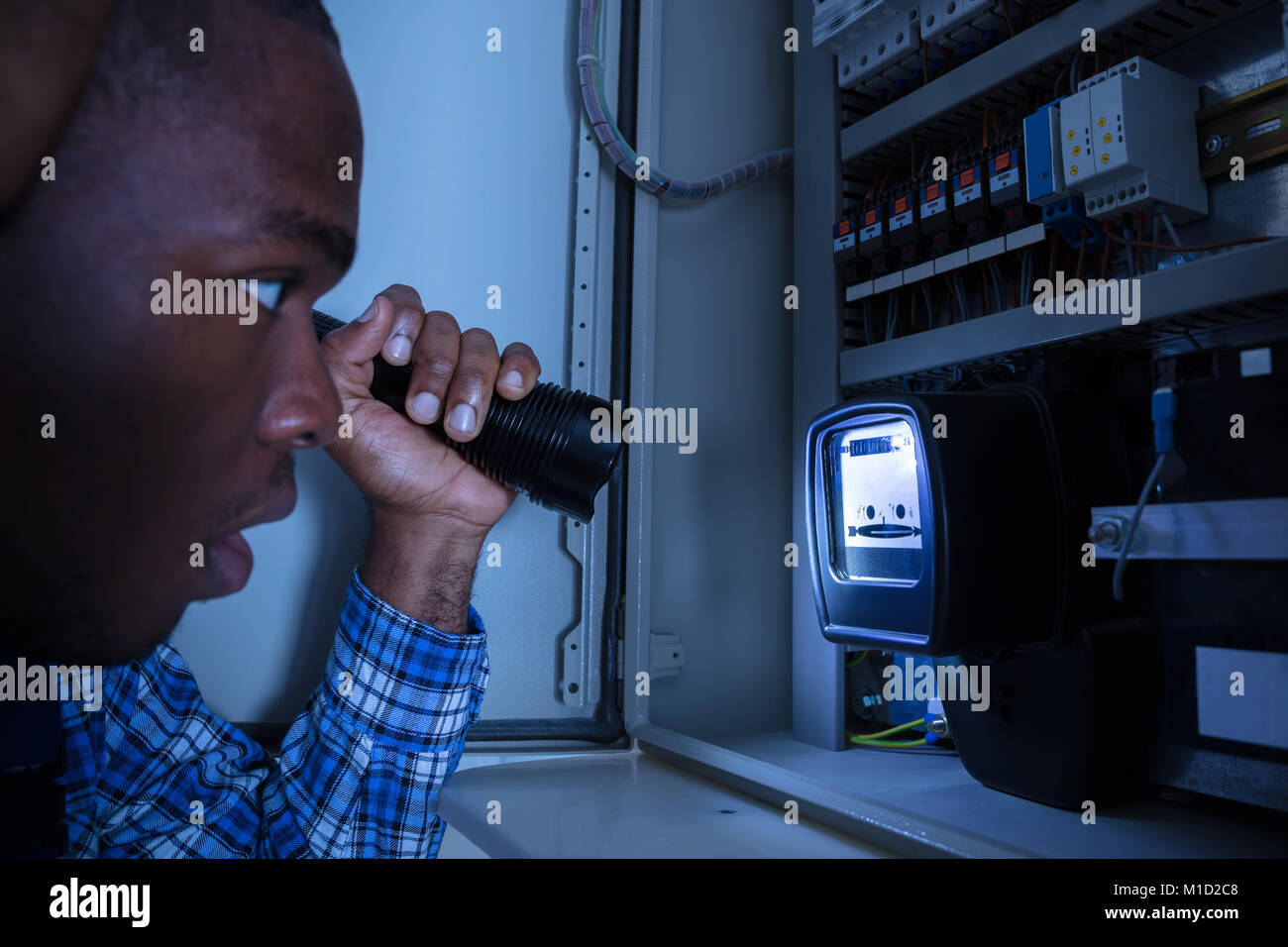 Close-up Of A Electrician Examining A Electric Meter With A Torch - Stock Image