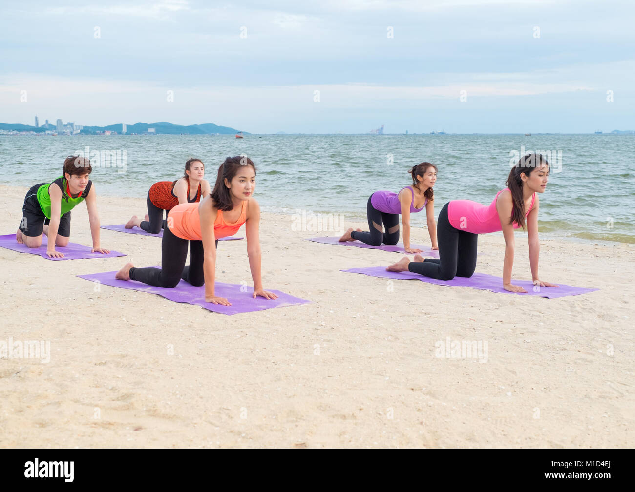 Yoga class at sea beach in evening sunset ,Group of people doing cat poses with clam relax emotion at beach,Meditation - Stock Image