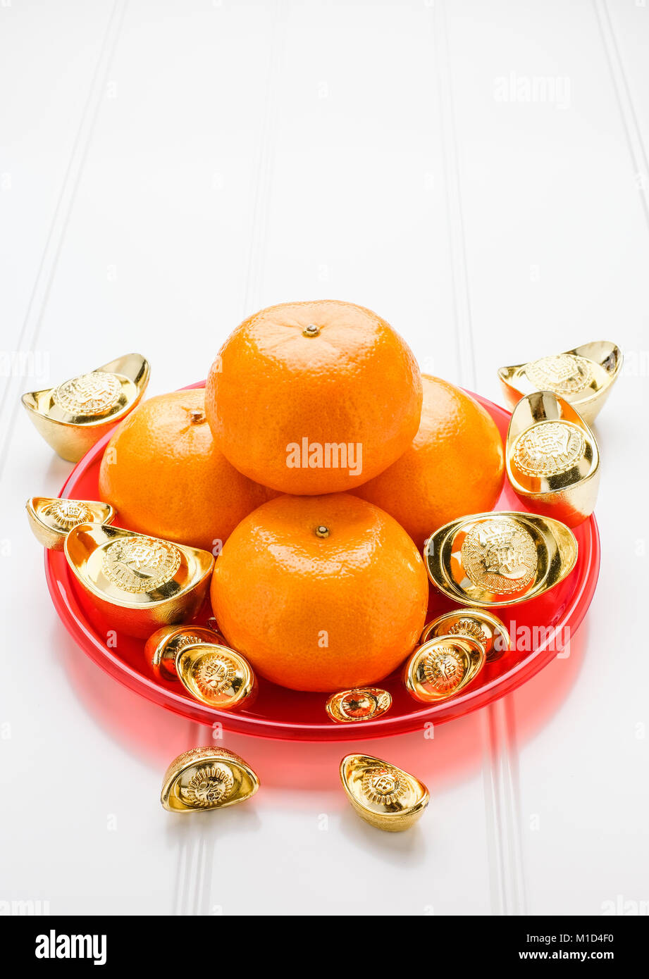 Chinese New year,gold ingots and tangerine oranges on white wood table top,Chinese Language ingot mean wealthy - Stock Image