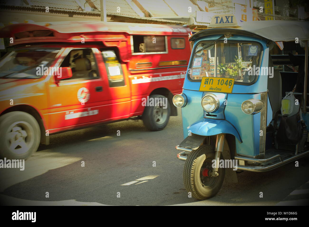 A blue tuk-tuk and a red songthaew taxi in Chiang Mai, Thailand. 24-Jan-2018 - Stock Image