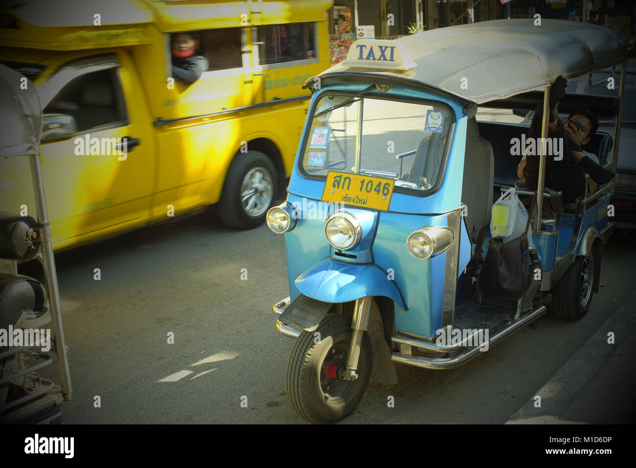 A blue tuk-tuk and a yellow songthaew taxi in Chiang Mai, Thailand. 24-Jan-2018 - Stock Image