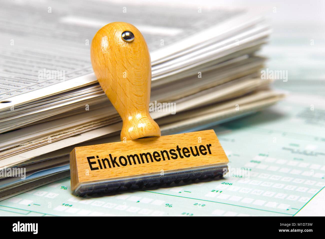 Einkommensteuer markiert auf Holzstempel vor Stapel Steuerformulare Stock Photo