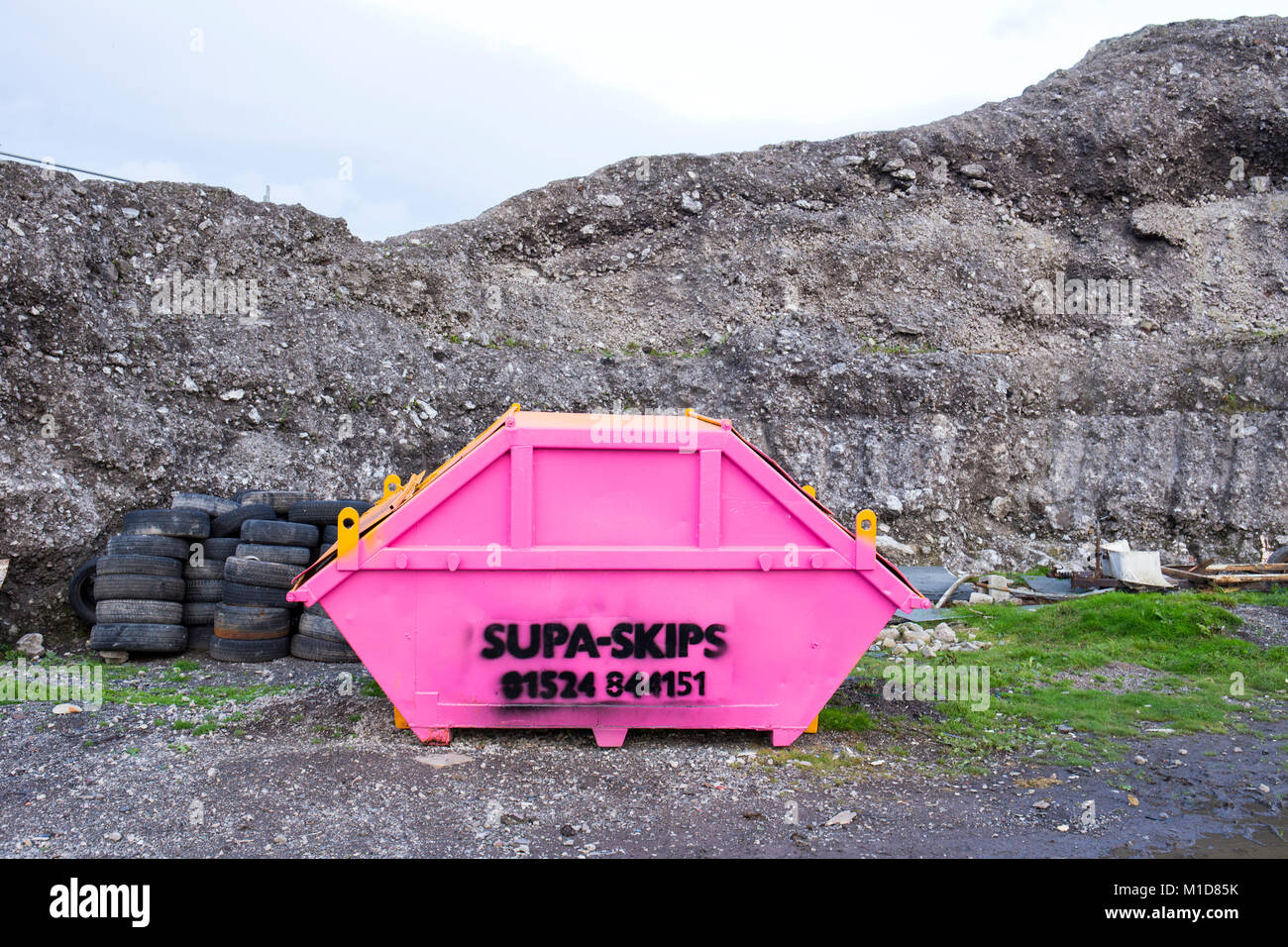 An empty pink coloured skip in the countryside UK - Stock Image