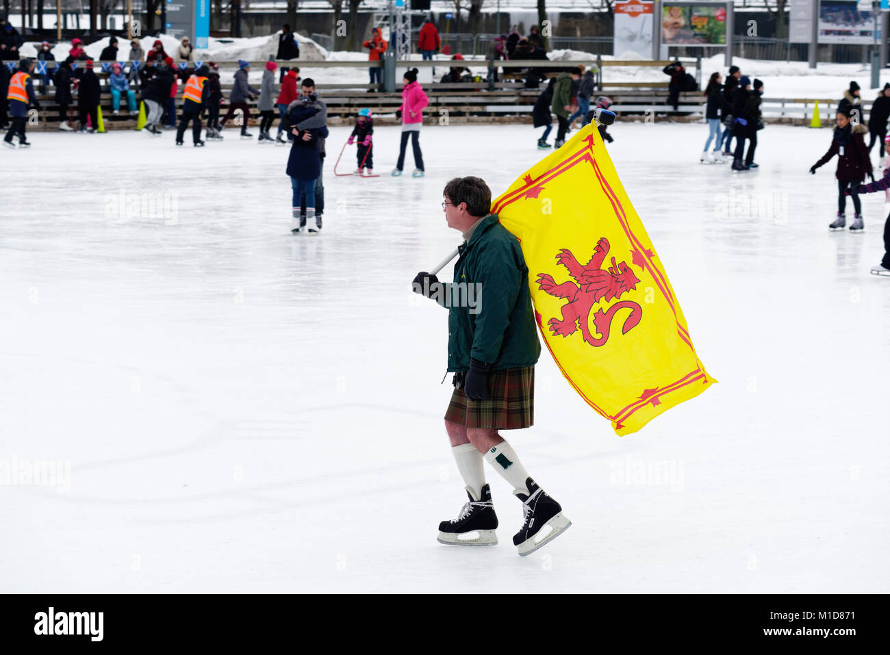 A skater in Montreal Old Port carrying the Scottish Royal Standard, celebrating their Scottish ancestry in the annual - Stock Image