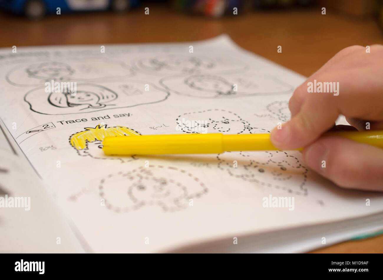 A child's hand writes and displays English letters in a notebook and alphabet with a pencil and felt-tip pen. - Stock Image