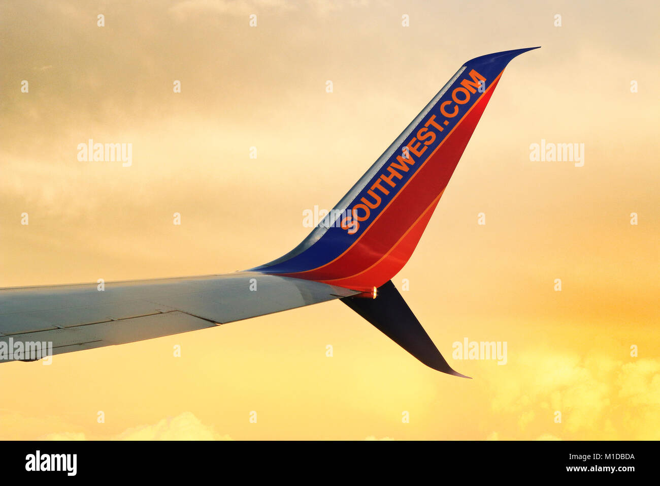 Winglet of Beoing 737 plane bearing Southwest Airline logo and website flying with sunset clouds background. Boeing - Stock Image