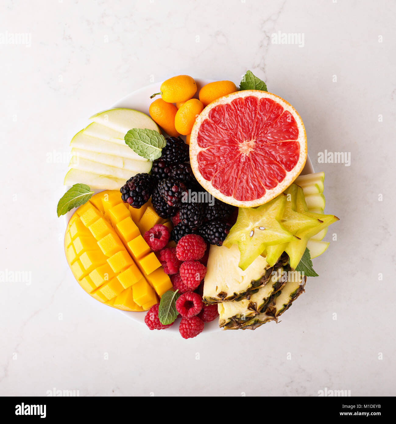 Fruit plate with mango, grapefruit and berries - Stock Image