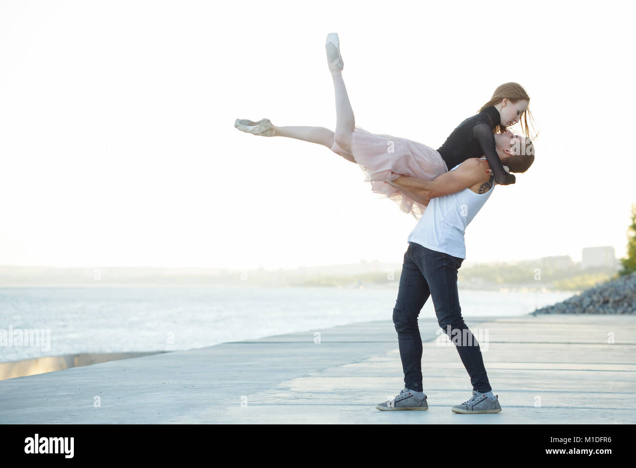 Slender ballerina dances with a modern dancer. Dating lovers. Passion and romance of dance. Performance on the streets. - Stock Image