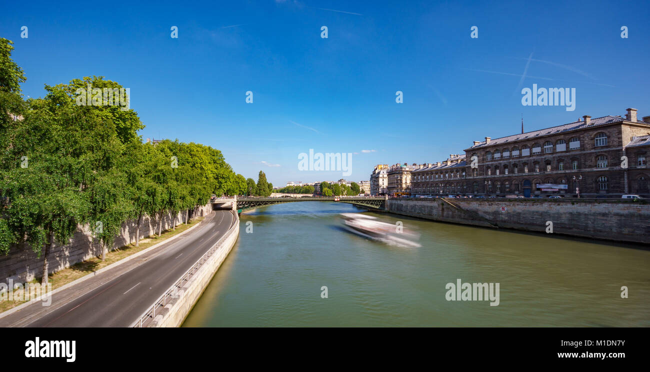 Blurred tourist boat over Seine river and road in Paris - Stock Image