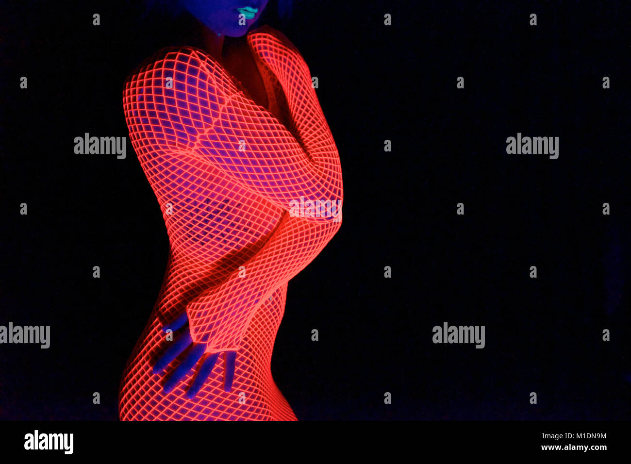 Pretty girl in a studio with black background and UV lighting Stock Photo