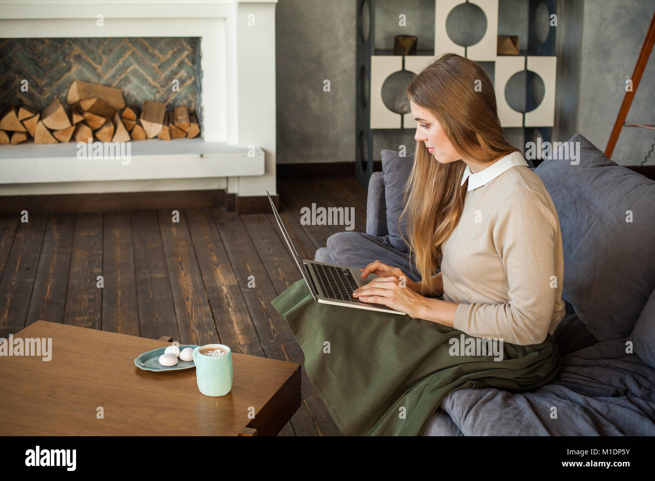 Young Businesswoman Using Laptop and Sitting on Sofa at Home Office Stock Photo