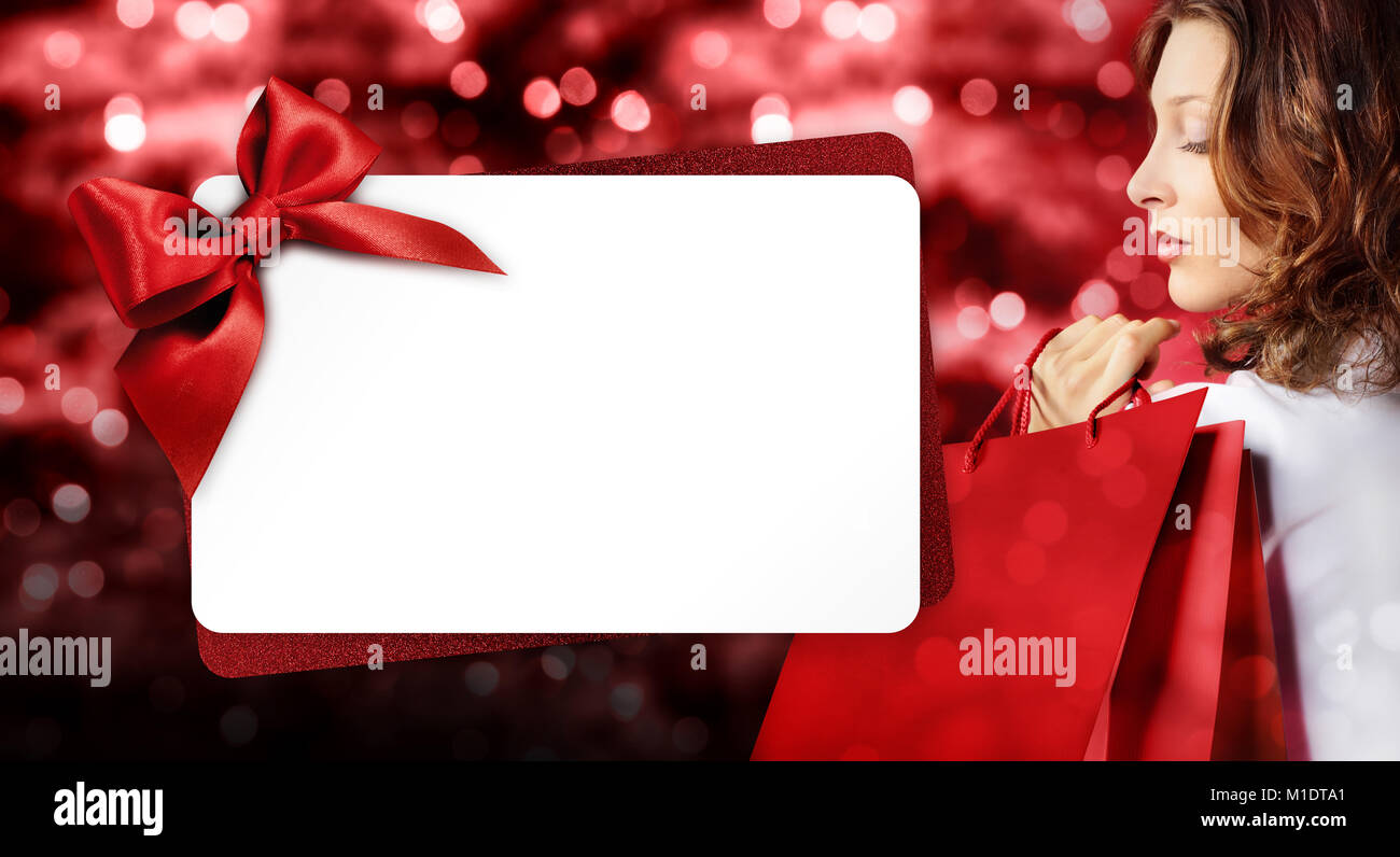 christmas shopping, woman with bag and gift card template on blurred bright lights background, banner template with - Stock Image