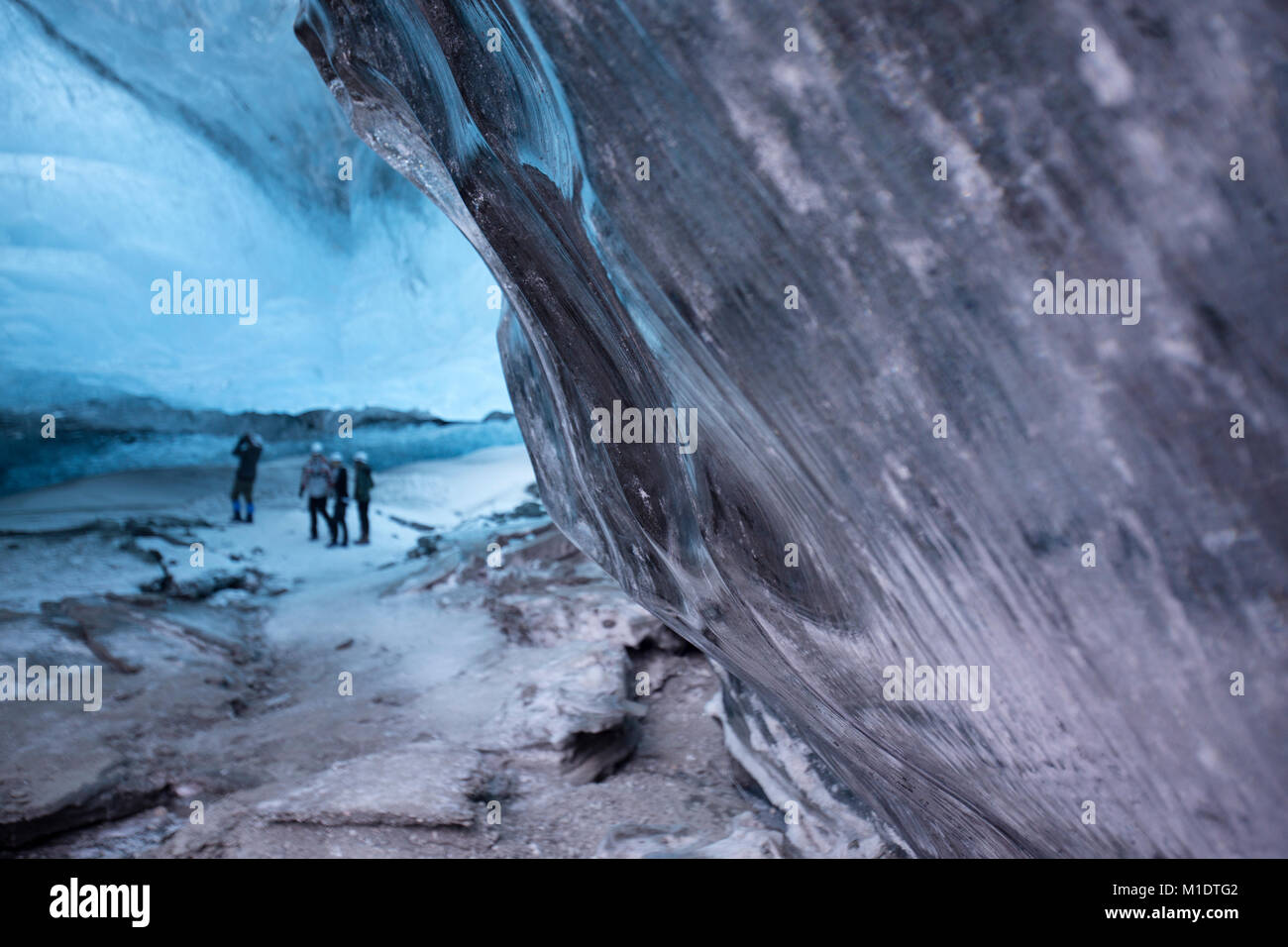 Ice Cave in south east Iceland, tourists with a tour guide - Stock Image