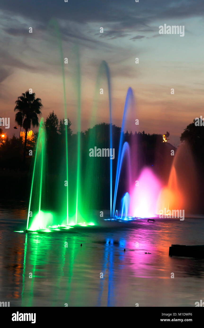 Isla Magica (Magic Island) Theme Park, Lake with water jets at dusk, Seville, Region of Andalusia, Spain, Europe - Stock Image