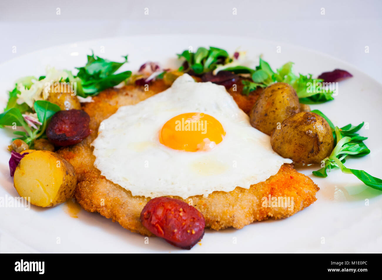 Schabowy. Breaded pork chop with fried egg and roast potatoes - Stock Image
