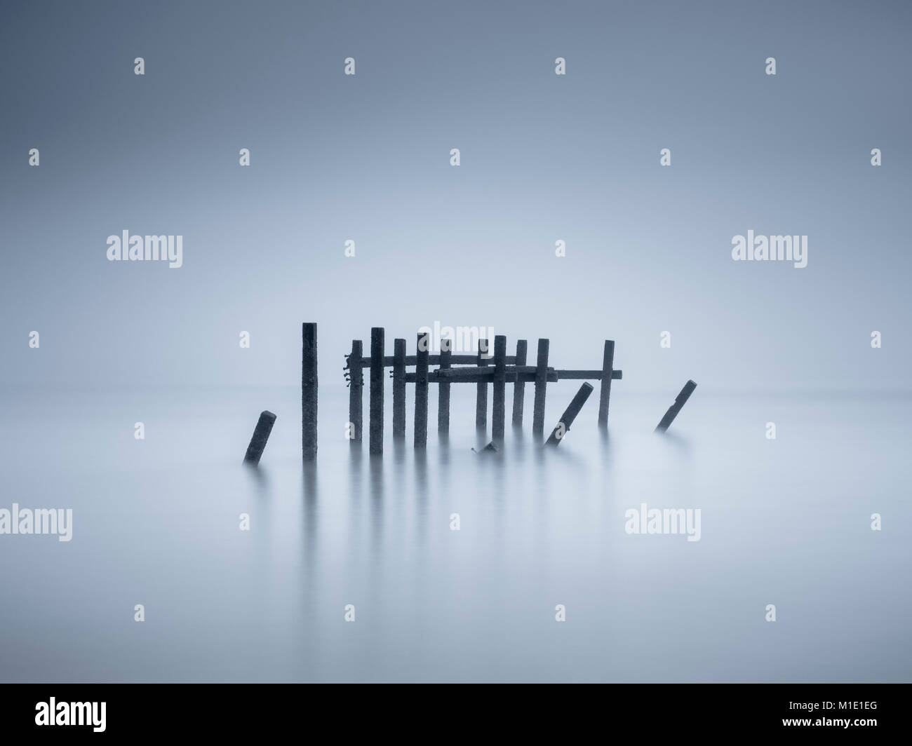 Remains of sea defences on a misty morning at Happisburgh. - Stock Image