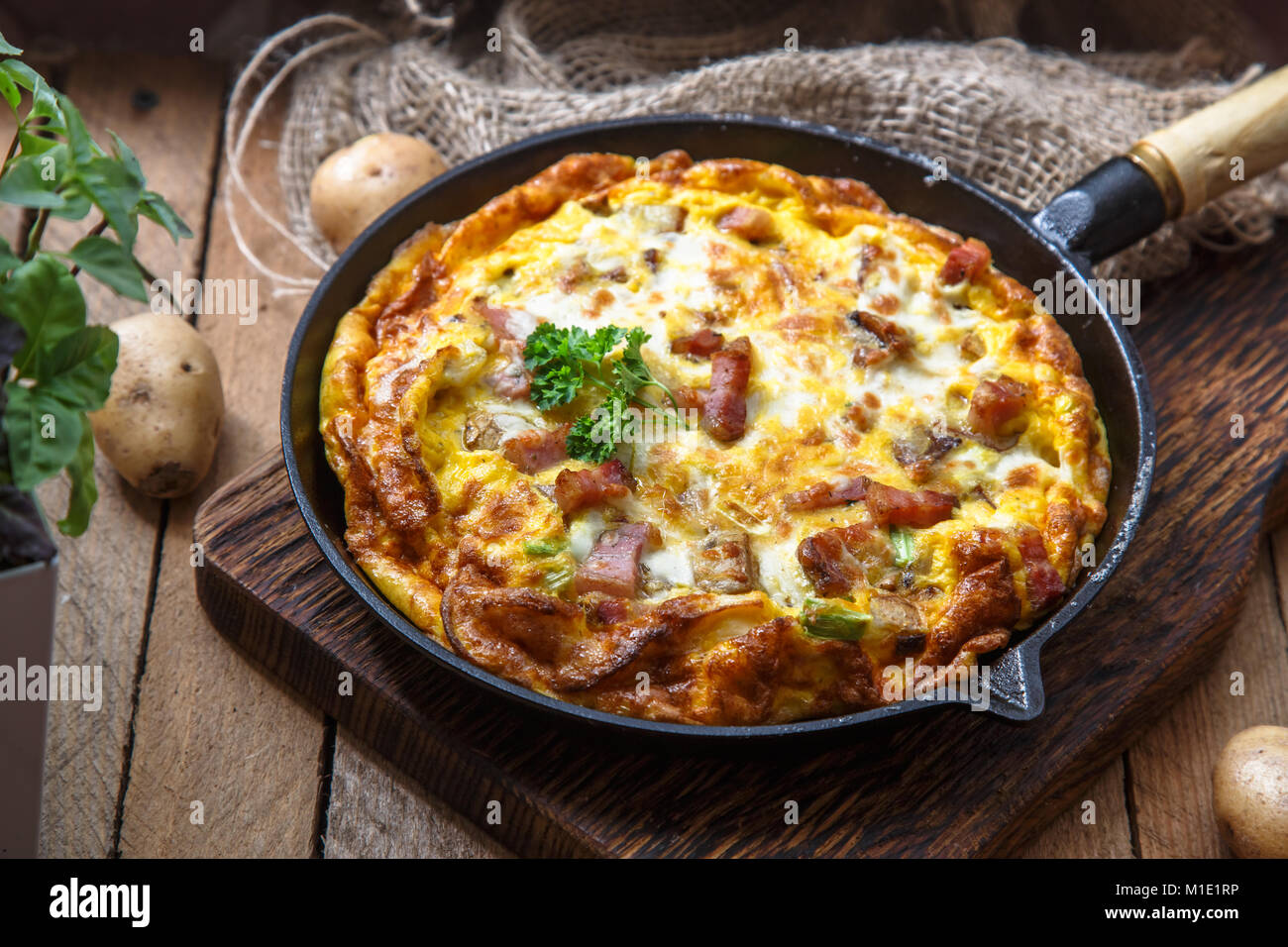 French omelette Savoyarde with bacon, cheese and leeks in fry pan, rustic - Stock Image