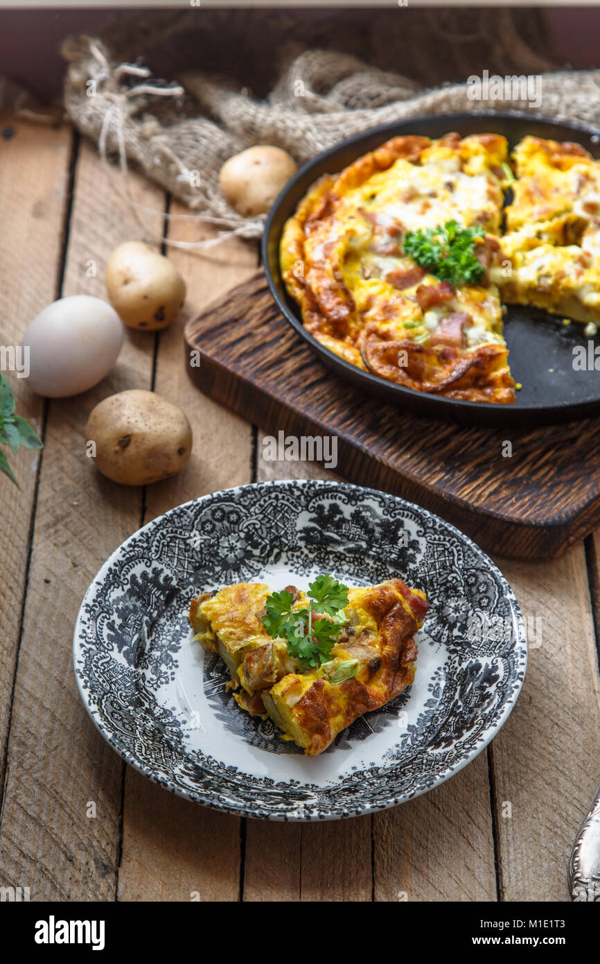 A piece of french baked omelette Savoy with ham, cheese, potato and leek on a plate, rustic style, top view - Stock Image