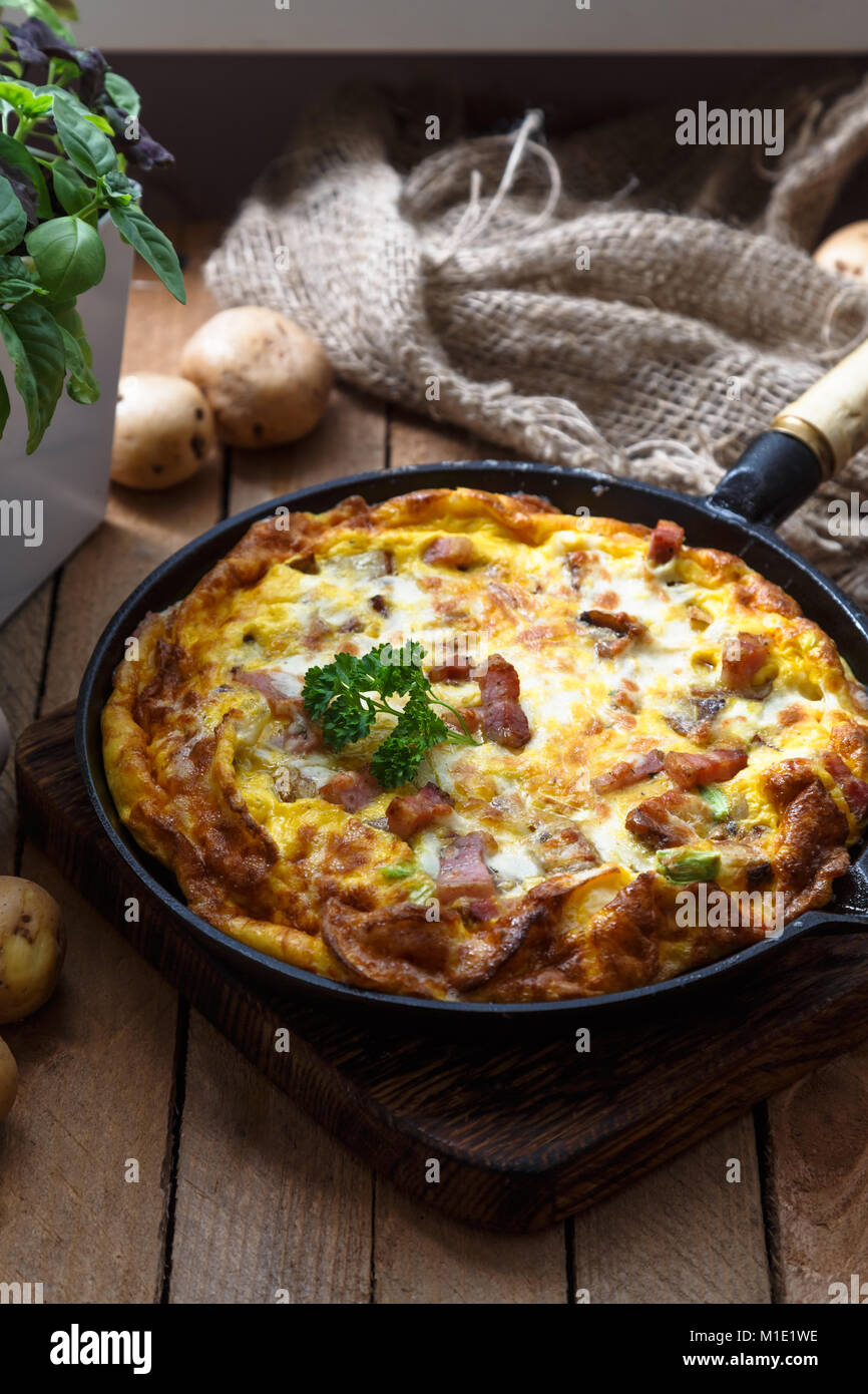 Baked omelette with bacon and cheese in a pan, close view - Stock Image