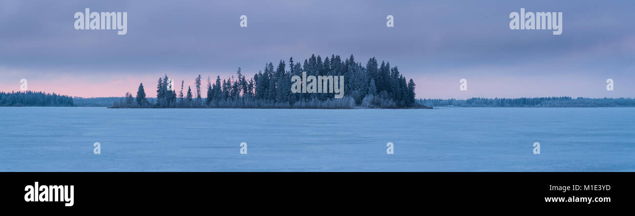 Panorama of frozen lake winter landscape with snow and forest, Elk Island National Park, Canada - Stock Image