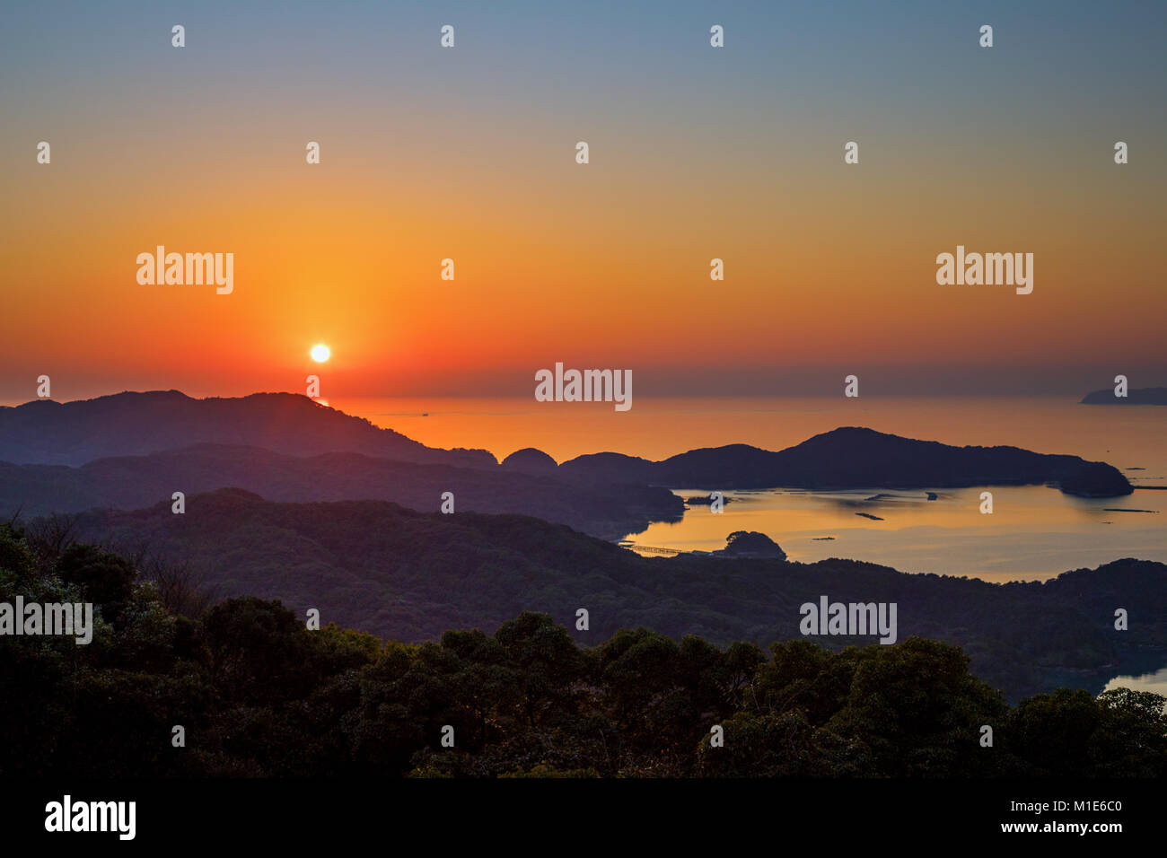The orange sun setting over the calm, flat ocean with the silhouette of the islands of Sasebo, Japan Stock Photo
