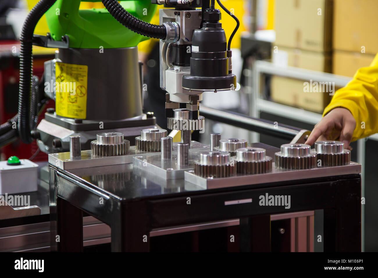 Worker operating 2D sensor robotic assembly machine - Stock Image