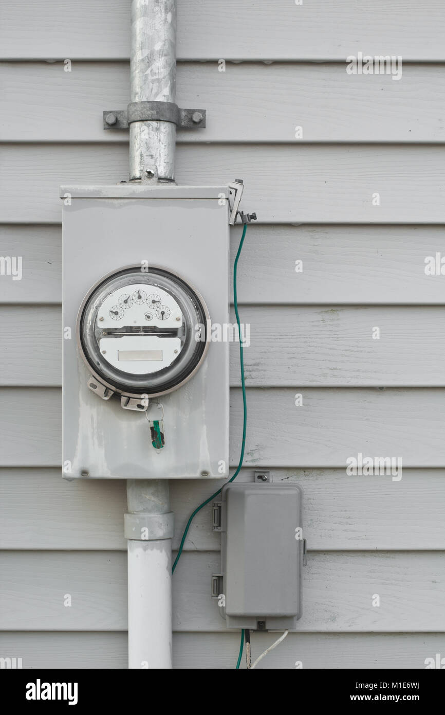 Electricity usage  meter on house siding. - Stock Image