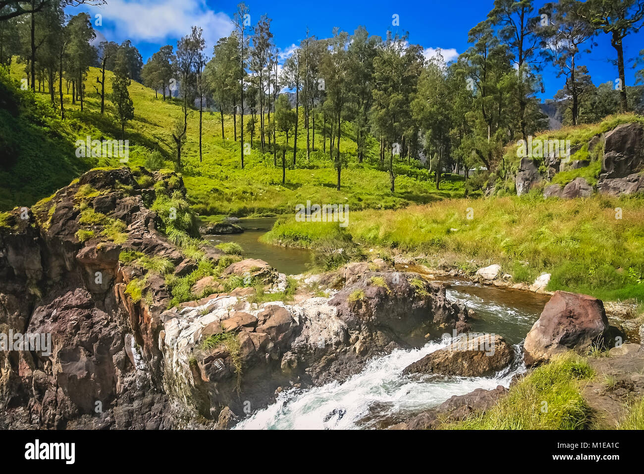 River ending in a waterfall with a water coming out of crater lake of Gunung Rinjani volcano, Lombok island, Indonesia - Stock Image
