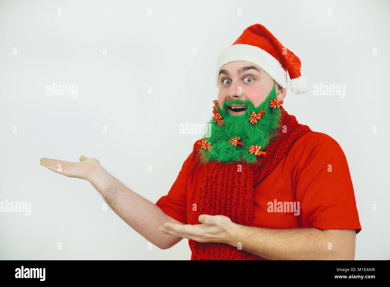 Santa Clause in red clothes with green beard decorated with red bows shows something - Stock Image