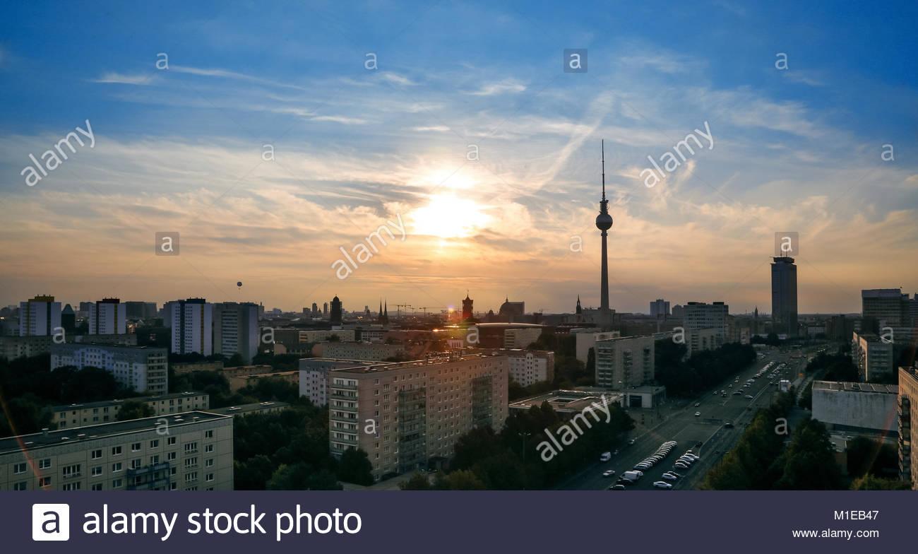 Ein Stadtpanorama aus Berlin mit Fernsehturm entlang der Karl-Marx-Allee mit grossen Mehrfamilienhaeusern am Ende - Stock Image