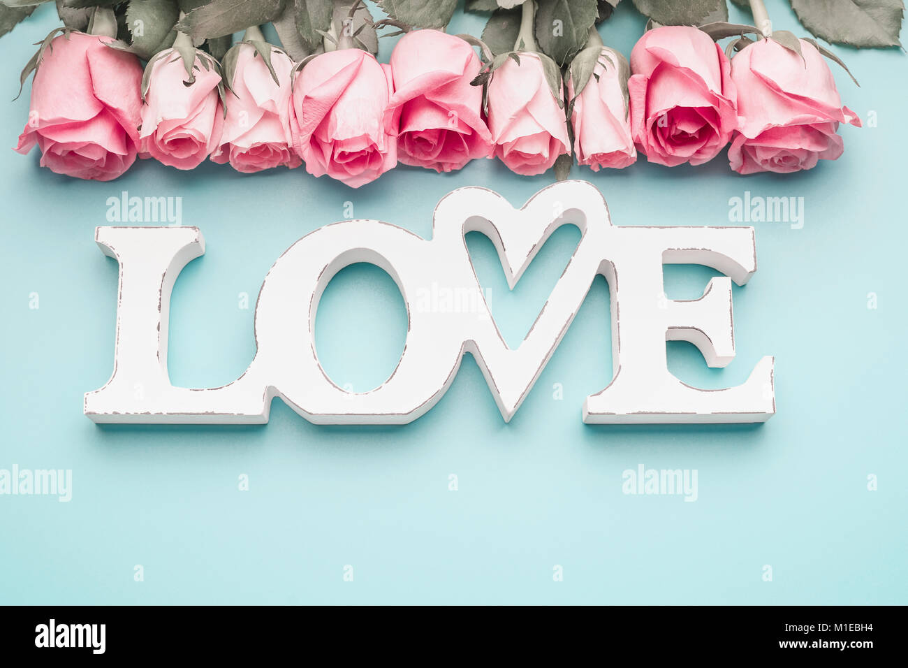 White Word Love With Pastel Pink Roses On Turquoise Blue Background