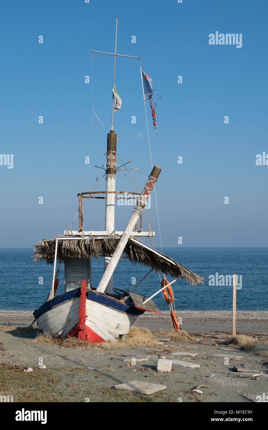 Red blue and white old fishing boat beside the calm aegean pelagus a sunny winter day - Stock Image