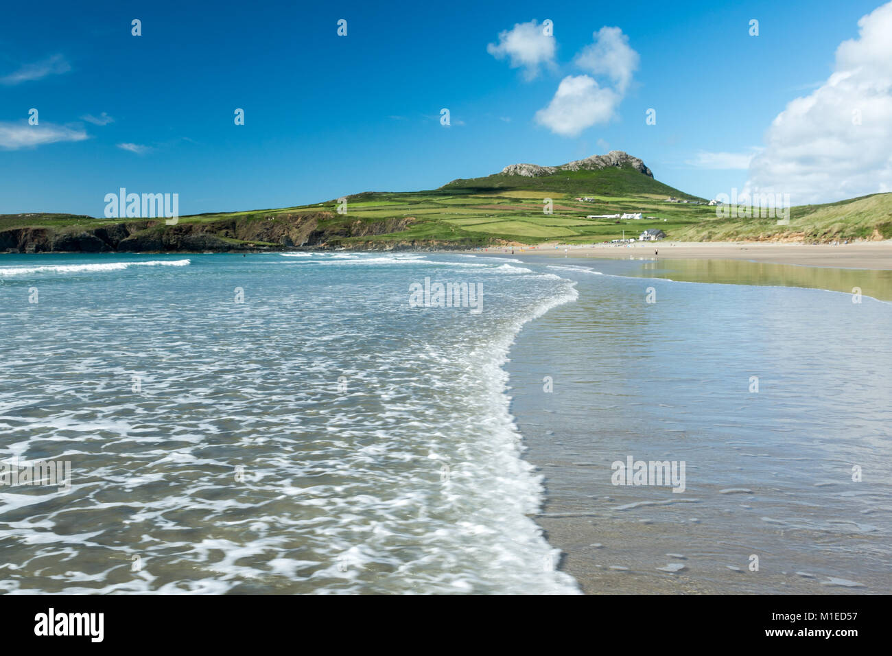 A gentle wave rolls over the sands of Whitesands Bay, near St Davids, Wales, under a blue sky with fluffy white - Stock Image