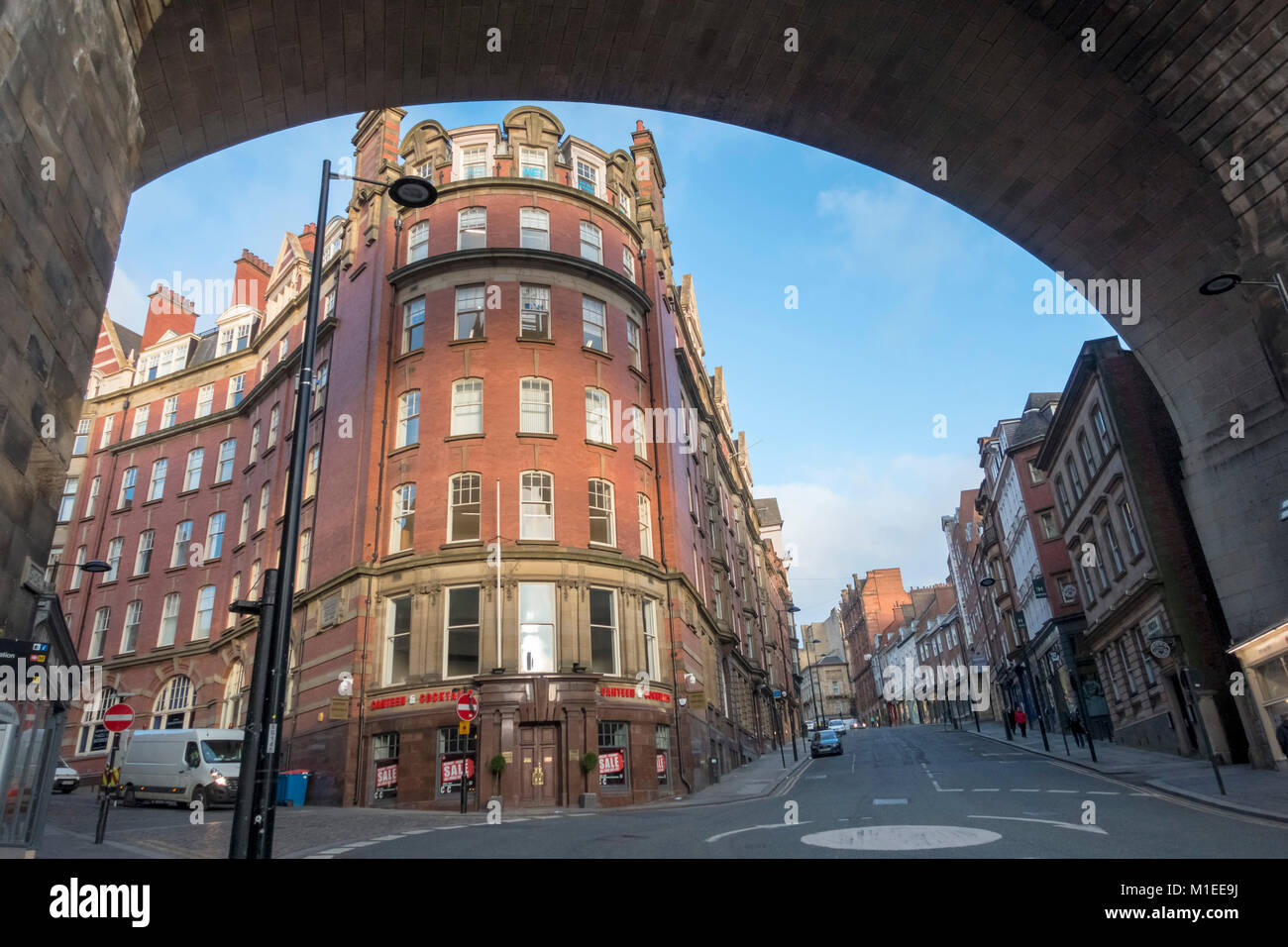 Looking up Dean street, Newcastle upon Tyne, under a high railway arch. - Stock Image