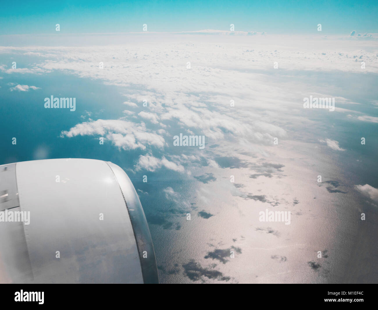 Aerial view of blue ocean and clouds from airplane window Stock Photo