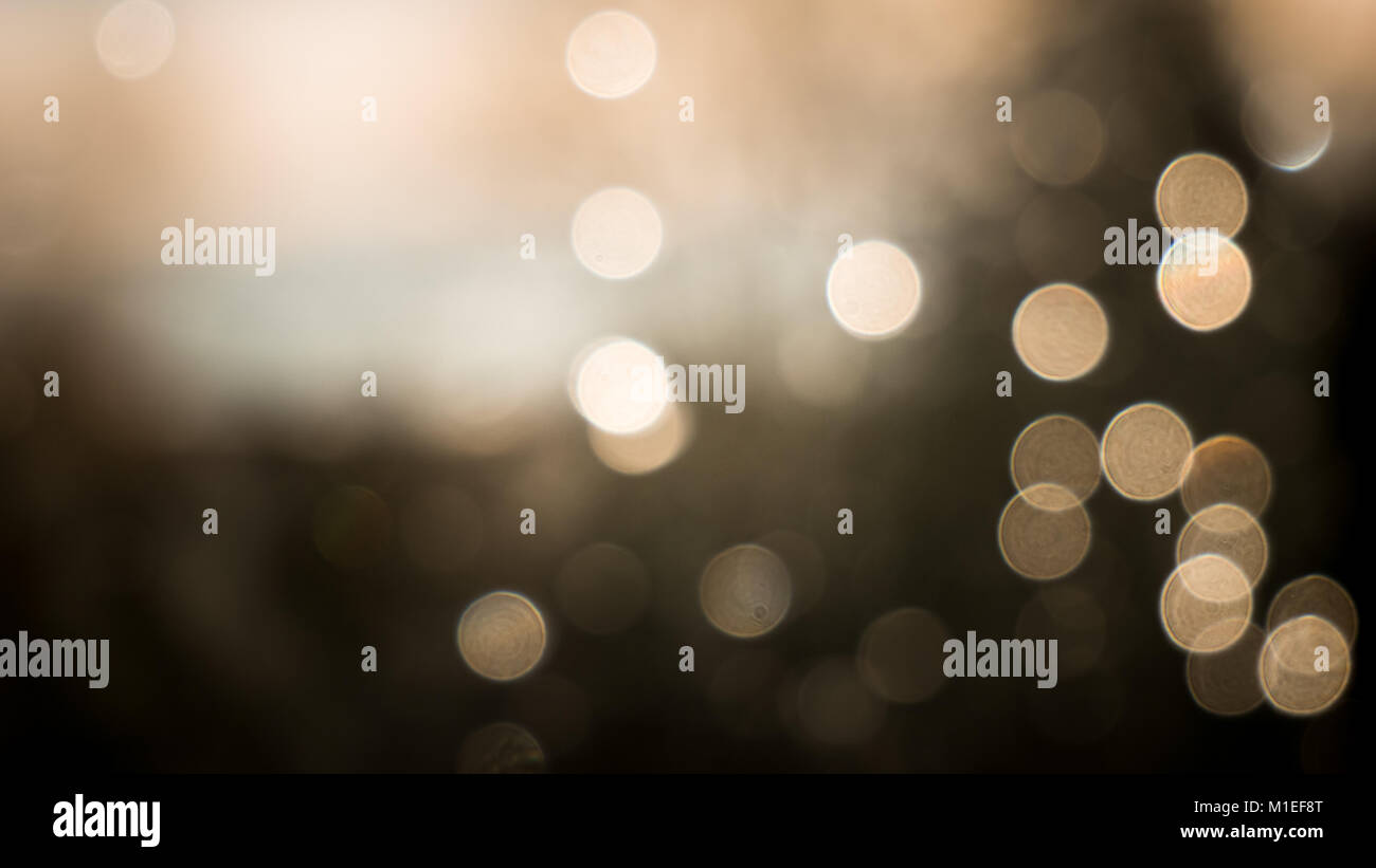 Bokeh effect of raindrops on a window. Sepia coloured to give it a more festive appearance. - Stock Image
