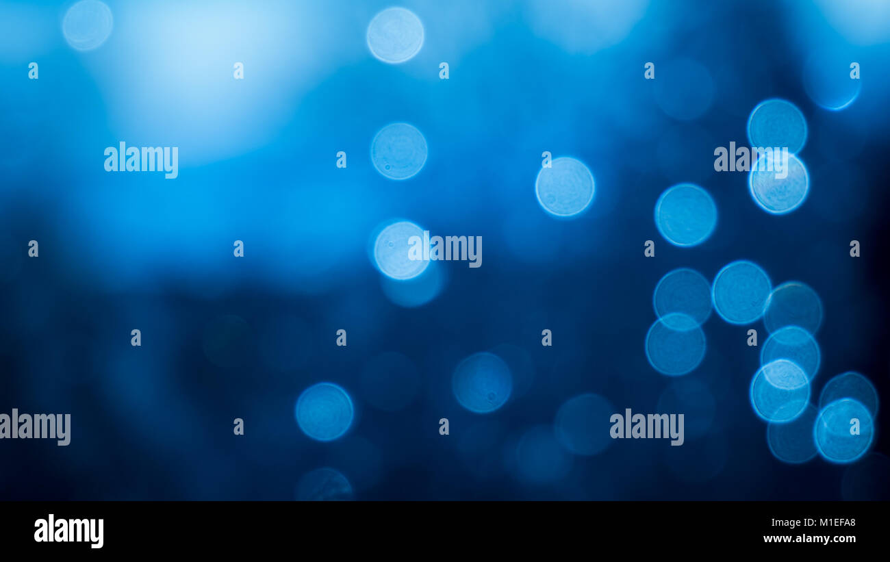 Bokeh effect of raindrops on a window. Blue comes from the sky in the background. - Stock Image