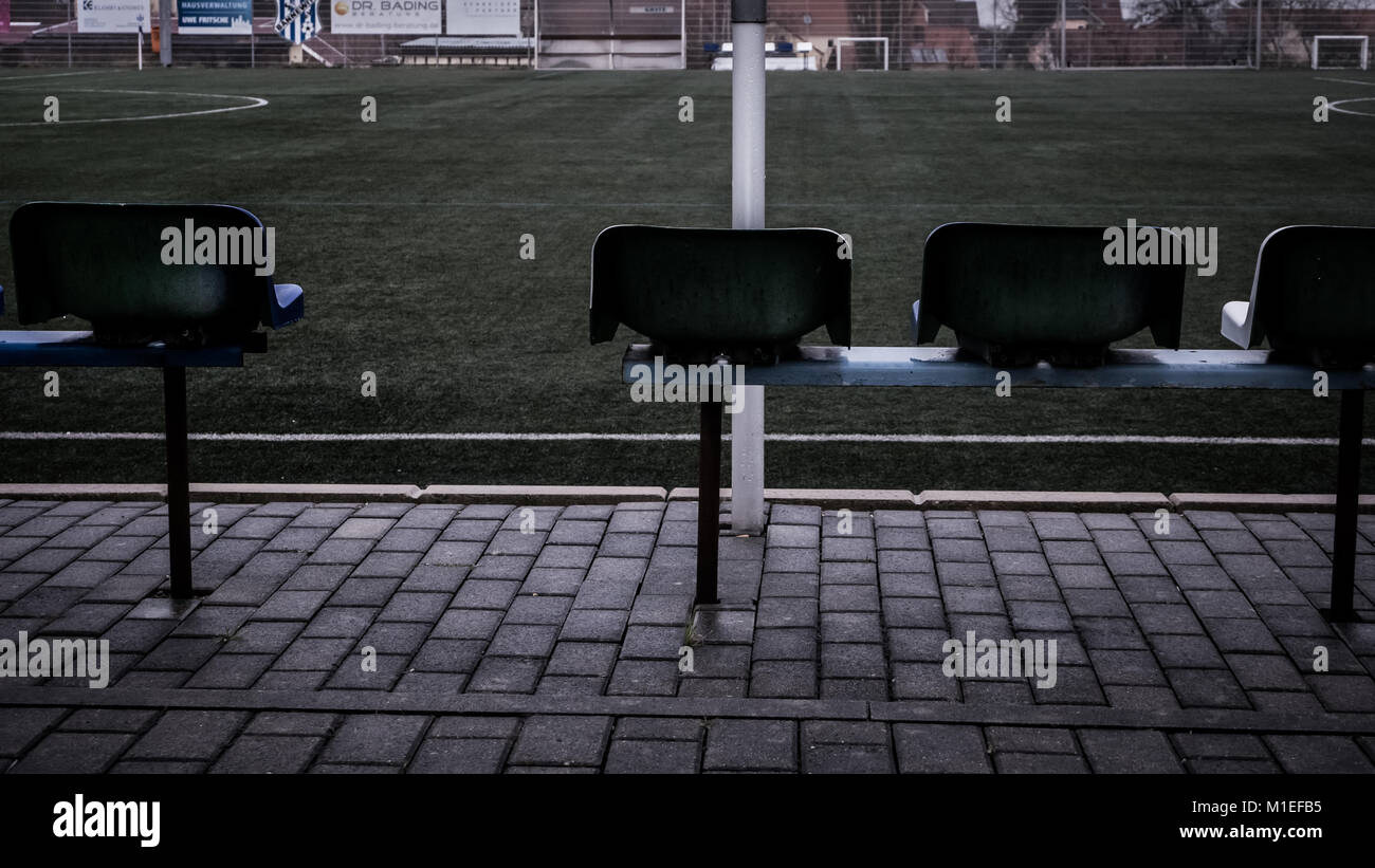 Emtpy soccer field and chairs/seats in a small community. Rainy and grey weather. Bad mood. - Stock Image