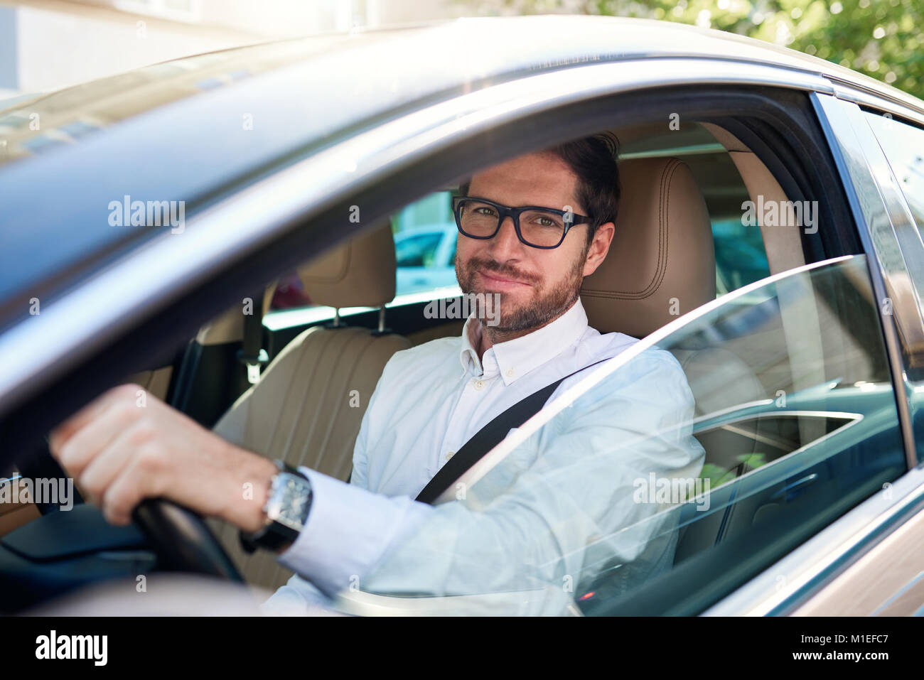 Smiling young man driving his car through the city streets - Stock Image